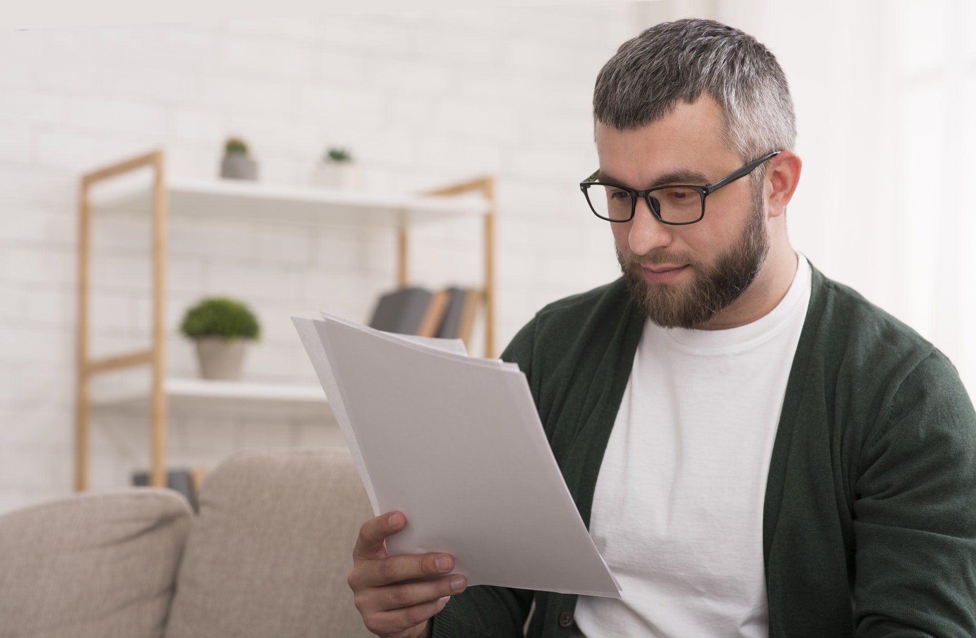 Concentrated man reading printed article, education at home