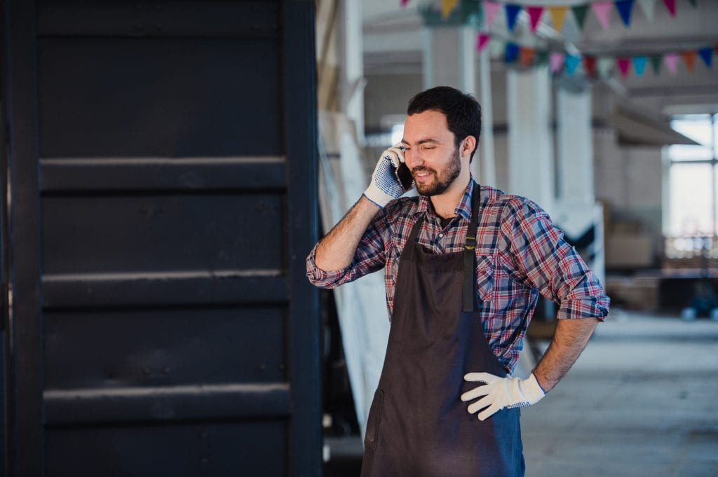 Smiling bearded man wearing gloves, owner of a small woodwork business, standing in his workshop