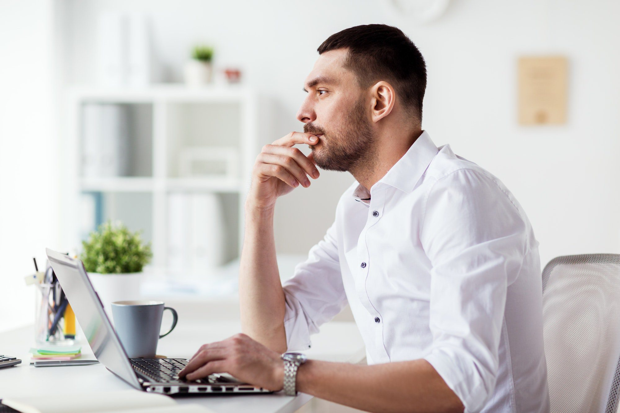 businessman with laptop thinking at office