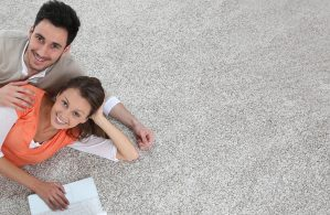 Couple laying on carpet of brand new renovated flat, template