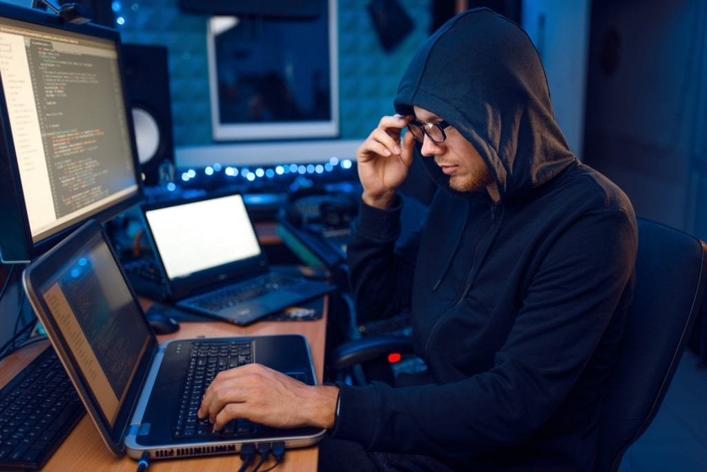 Hacker in hood at his workplace, corporate hacking